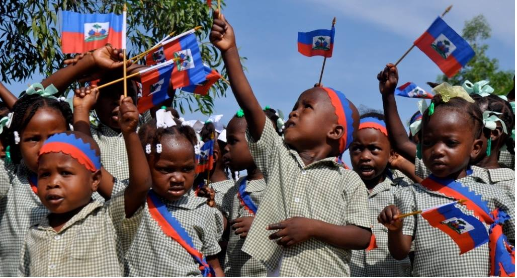 Haïtiaanse kinderen zwaaien met vlaggetjes