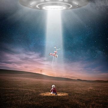 Klein kindje dat zijn fietsje ziet meegenomen worden door een ufo
