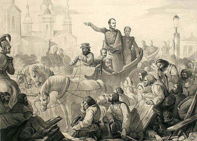 De tsaar die in paard en wagen tussen een woelige mensenmassa door rijdt. Hij spreekt de menigte toe en de mensen buigen voor hem.