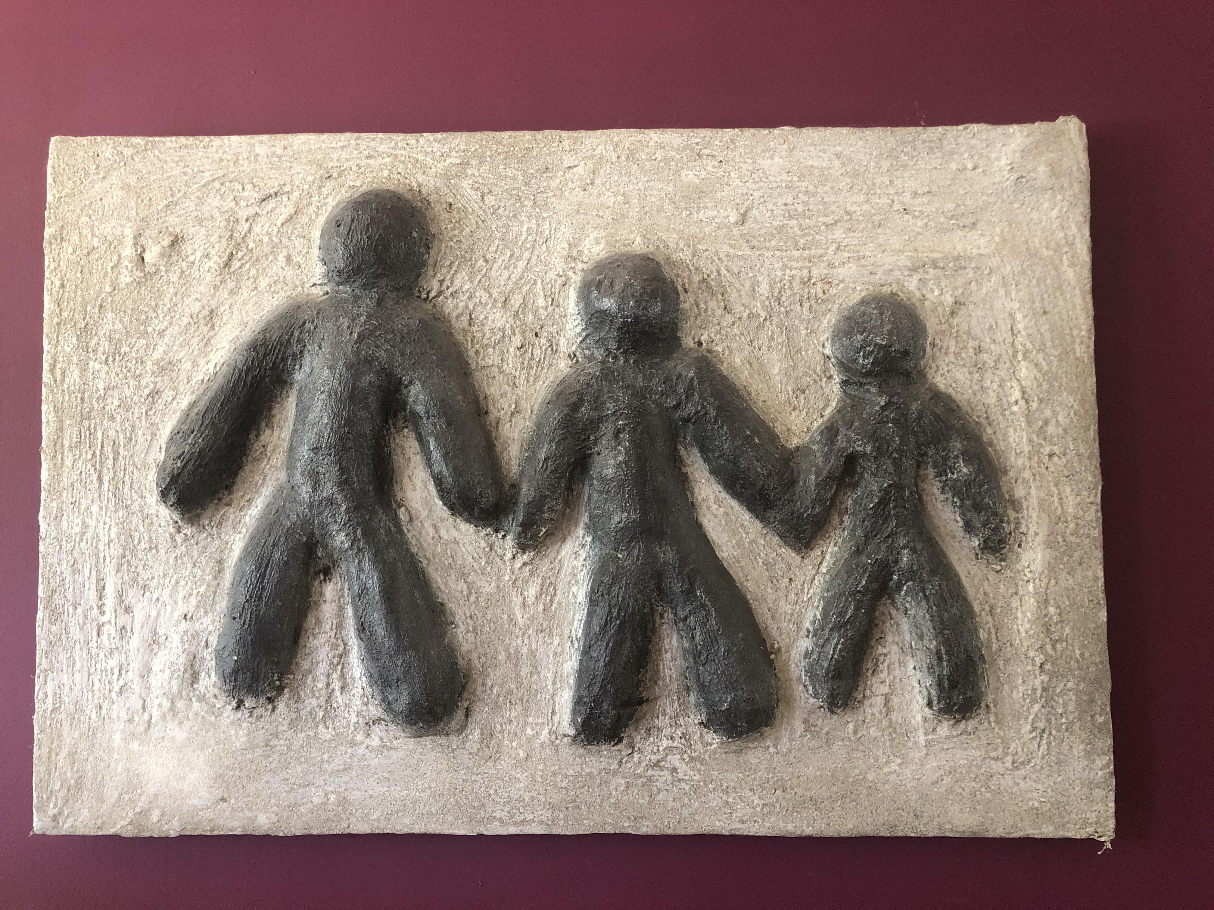 Je ziet een kunstwerk met drie mannetjes op.