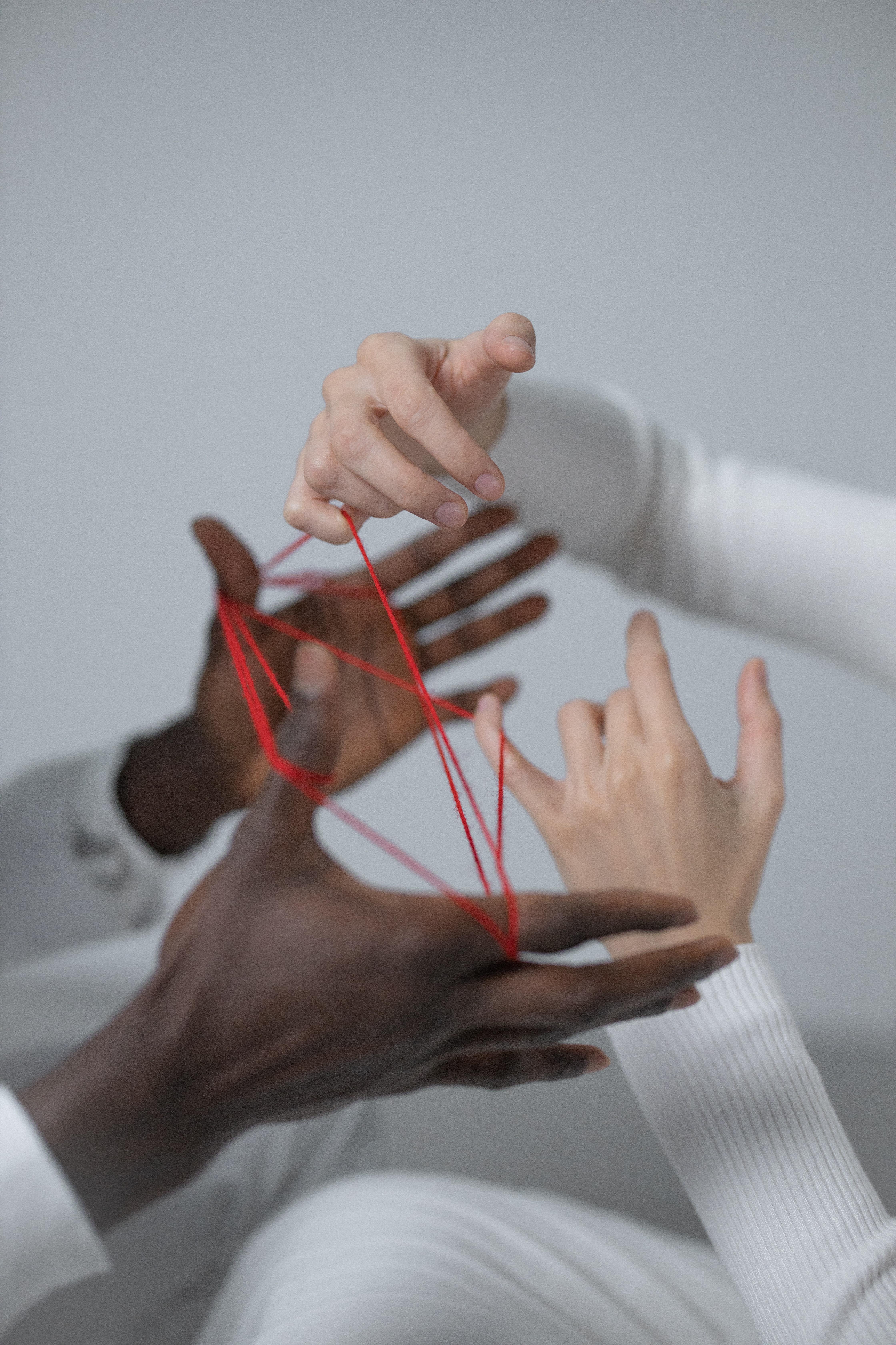 Handen verwikkelt in een web van rode draden