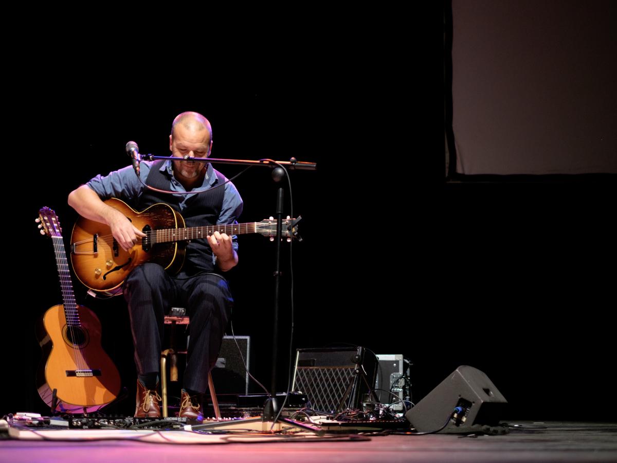 Een gitarist op het podium.