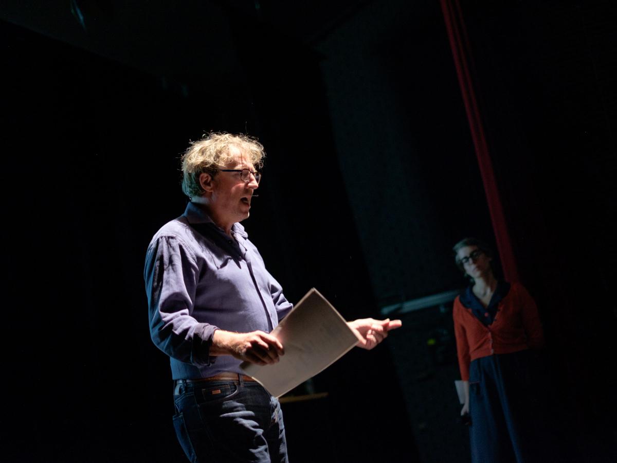 Een man die een lezing geeft op een podium.