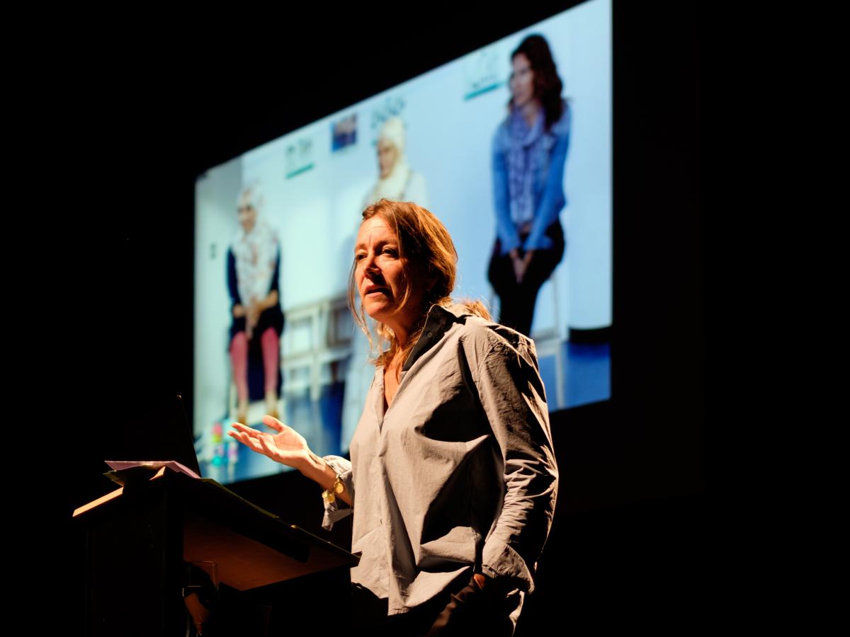 Een vrouw die uitleg geeft met een powerpointpresentatie op de achtergrond.