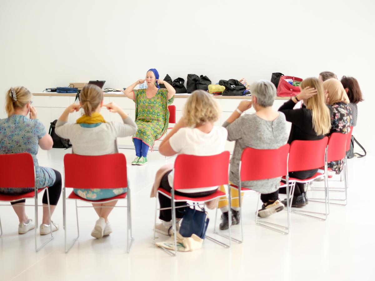 Een groep mensen die onder leiding van een begeleider bepaalde bewegingen uitoefenen.