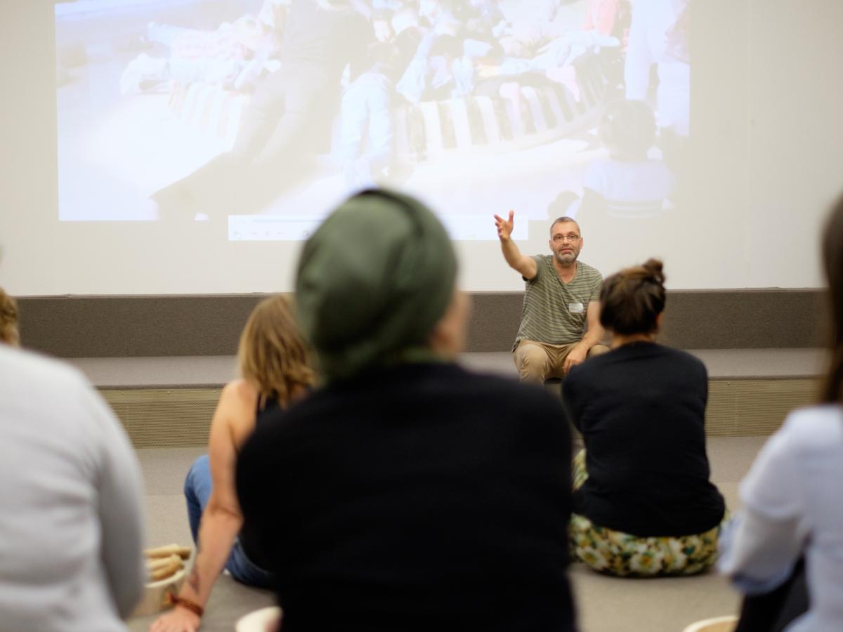Een zittend persoon die aan een groep mensen een lezing geeft met een geprojecteerd beeld op de achtergrond.