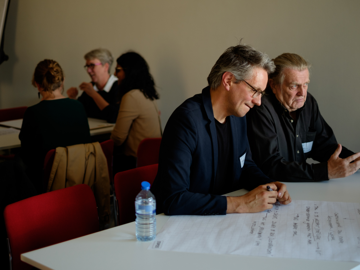 Twee mannen aan een tafel die brainstormen.