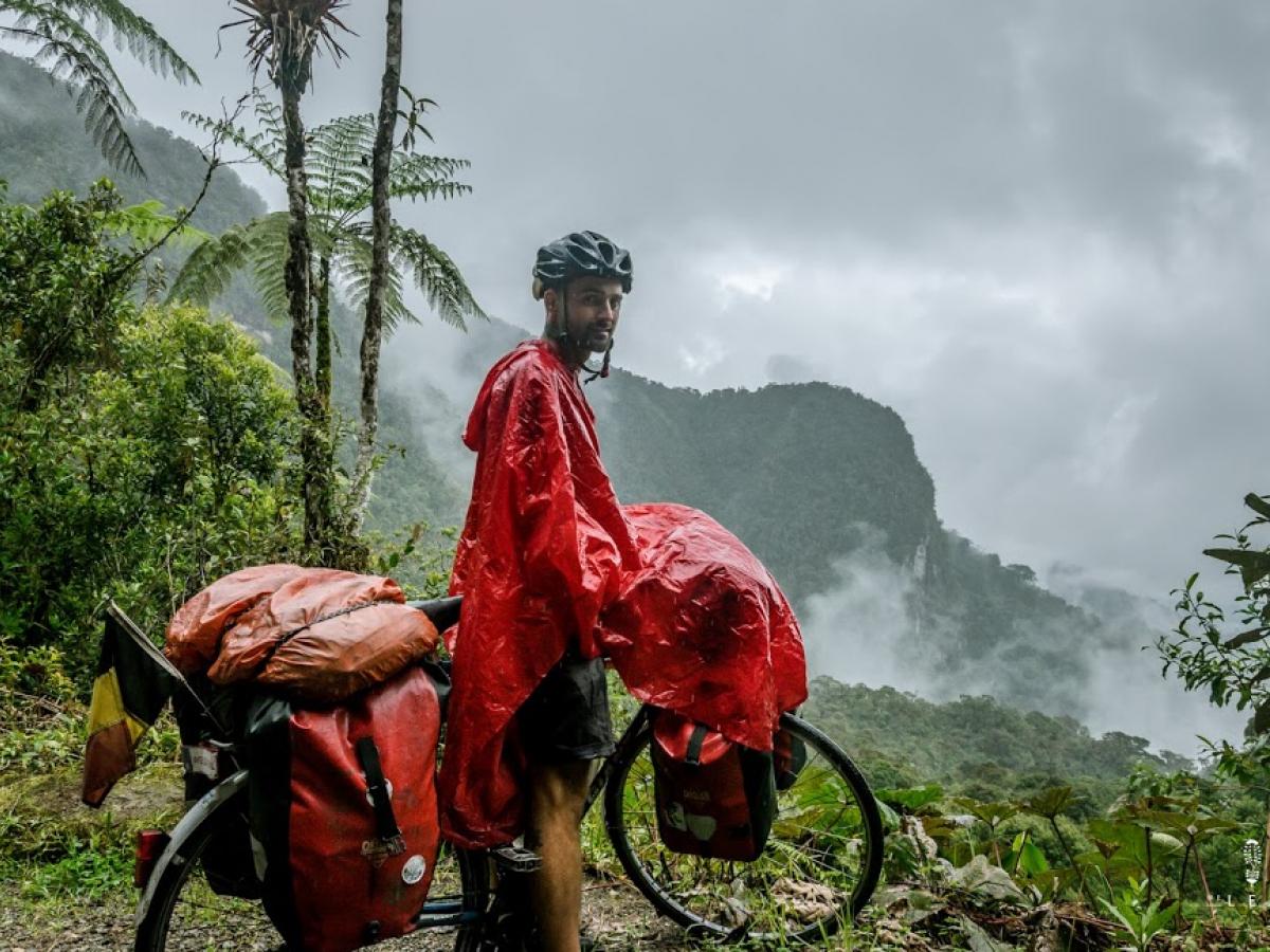 Olivier Van Herck fietst door Colombia. Hij beschermt zich tegen de regen met een poncho, al blijven de tassen niet gespaard door het regenseizoen.