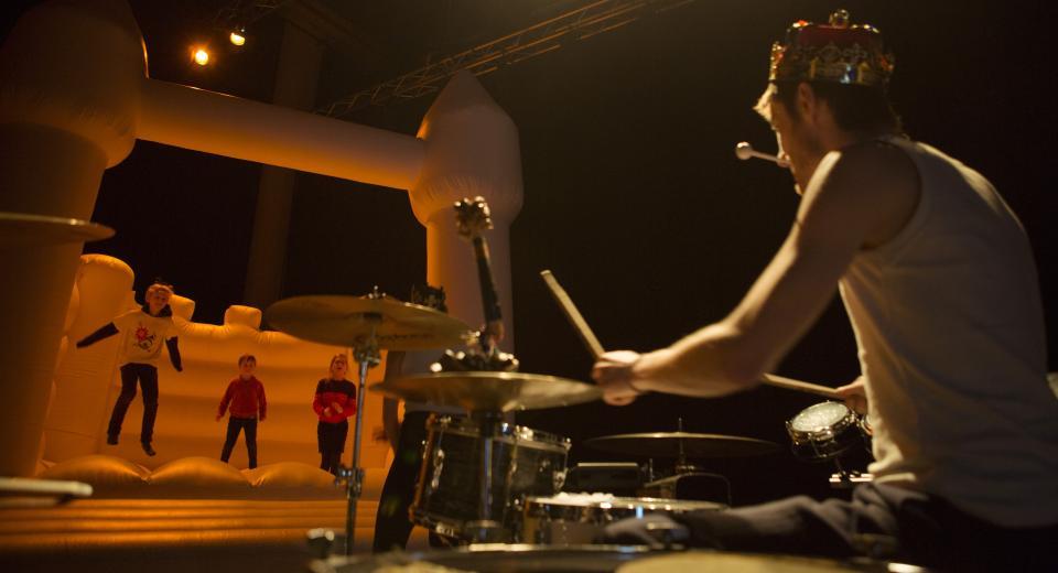 Kinderen op muzikaal springkasteel met drummer