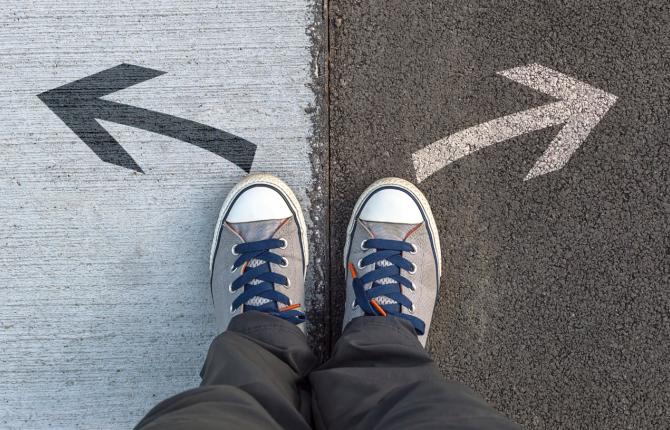 Een persoon staat voor 2 pijlen op de grond die naar een andere richting uitwijzen