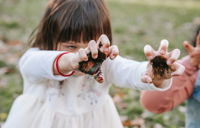 kind met modder aan vingers